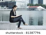 Asian Business woman using a touch screen tablet in City - stock photo