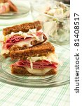 Traditional reuben sandwich cut into quarters served with potato salad - stock photo