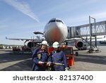 Stock photo two air mechanics engineers with large airliner in background airport ground activities 82137400