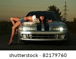 Young sexy woman on car hood - stock photo