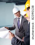 Young people in business suits and helmets on a construction site - stock photo