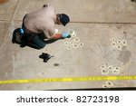 a crime scene detective investigates and gathers evidence at a drive by shooting crime scene. - stock photo