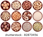 assortment of nuts and seeds in ceramic bowls isolated on white background - stock photo