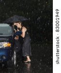 Woman locked out of her car in the rain - stock photo