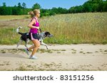 Stock photo woman runner running with a dog on country road 83151256