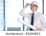 A young man in a shirt and a helmet on a construction site - stock photo