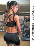 beautiful woman on excercise bike at the gym - stock photo