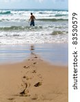 A man walking into the ocean with his footprints in focus - stock photo
