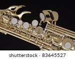 A gold and silver soprano saxophone isolated against a black background. - stock photo