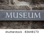 Grey Wooden Museum Sign on Stone Wall - stock photo