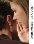 Woman whisper in ear man - stock photo