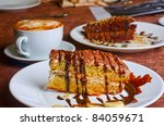 Dessert cakes with banana and coffee at table - stock photo