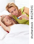 Woman checking her sick daughter's temperature laying on the bed - stock photo