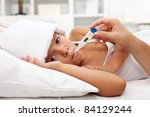 Sick child with fever laying in bed holding a thermometer between lips - stock photo
