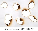 burnt holes in a paper - stock photo
