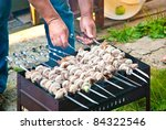man cooking kebab on a brazier | Shutterstock . vector #84322546