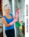 attractive housewife cleaning window at her home - stock photo