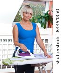 attractive woman ironing clothes in her home - stock photo