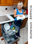 attractive housewife washing dishes in dishwasher in her home kitchen - stock photo