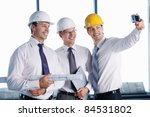 Business people in hard hats are photographed on site - stock photo