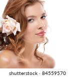 Attractive young beautiful woman with pink rose in the hair on white background - stock photo