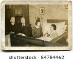 Vintage photo of family visiting bedridden grandmother - stock photo