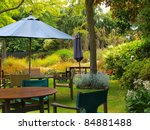 dining table in sunny garden patio with sunshade - stock photo