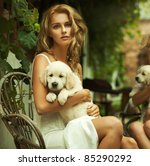 Portrait of a young blonde hugging a cute puppy - stock photo