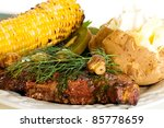 Food:  A grilled steak topped with mushrooms and dill, garden fresh corn on the cob and a steaming hot baked potato for dinner. - stock photo