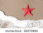 Starfish and ocean wave on sandy tropical beach - stock photo