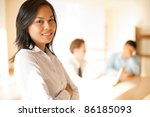 Attractive ambitious Asian businesswoman leader in white blouse, smiling, confident, looking at camera in high key office conference room table meeting with businessmen team. Horizontal copy space - stock photo