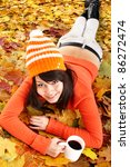 Girl in autumn orange leaves with cup coffe. Outdoor. - stock photo