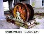 Old rusty mine shaft mechanism on dusty ground - stock photo