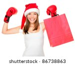 Christmas shopping boxing day concept with woman holding shopping bag wearing santa hat and boxing gloves. Funny fresh image of mixed race Asian Caucasian female model isolated on white background. - stock photo