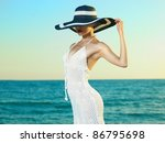 Photo of a beautiful young woman in a hat by the sea - stock photo