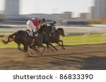Horse race in an urban environment with evening sunlight - stock photo