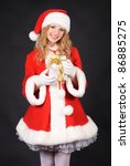 Christmas santa girl with gift isolated on black. Copy text. Christmas greetings card - stock photo