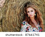 gorgeous young woman is resting by the hey - stock photo