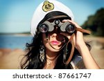 Sailor woman with binoculars is taking a walk on the seacoast - stock photo