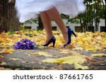 bride is dancing on the yellow leafs wearing her blue heels - stock photo