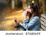Stock photo beautiful woman have lunch while strolling with her dog in the park 87680659