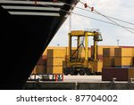 Forklift carrying one single container near a huge container ship (carrying more than 3000) in Antwerp world harbor - stock photo