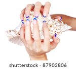 isolated body part shot of beautiful healthy young woman's manicured hands with shell on white - stock photo