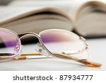 the reading glasses and open old book - stock photo