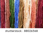 Wall of many colors of raw yarn for sale - stock photo