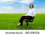 happy businesswoman sitting on chair over green field - stock photo