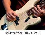 Hand of bass player while playing bass, colorful background - stock photo
