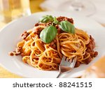 spaghetti with basil garnish in meat sauce. Shot with selective focus - stock photo