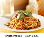 spaghetti dinner with basil garnish in meat sauce - stock photo