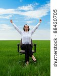 happy businesswoman sitting on chair over green meadow - stock photo